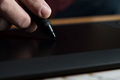 Hand Holding Graphic Pen Over Table Stock Image
