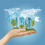 Hand holding a grass field and city of skyscrapers. Graphs and globe on background Royalty Free Stock Images