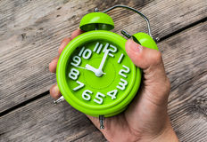 Hand Holding Green Alarm Clock Stock Photo