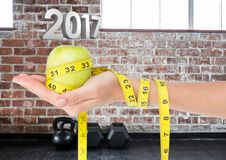 Hand holding green apple wrapped with measuring tape against 3D 2017 Stock Photo