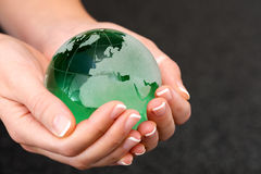 Hand holding green glass globe Stock Photography