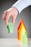 Hand Holding a Green Paper House. Hand of a business woman holding a green paper house next to row of houses in energy label colors royalty free stock photos