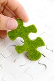 Hand holding a green puzzle piece Stock Photos