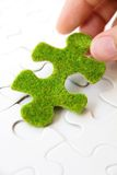 Hand holding a green puzzle piece Royalty Free Stock Photo