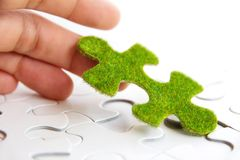 Hand holding a green puzzle piece Royalty Free Stock Images