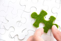 Hand holding a green puzzle piece Royalty Free Stock Photography