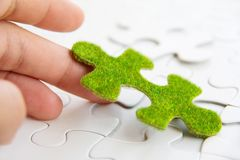 Hand holding a green puzzle piece Stock Photo
