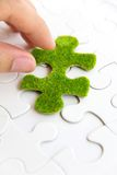 Hand holding a green puzzle piece Royalty Free Stock Photos