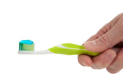 A Hand holding a Green toothbrush on white Royalty Free Stock Photo