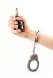 Hand holding a grenade in handcuffs Stock Image