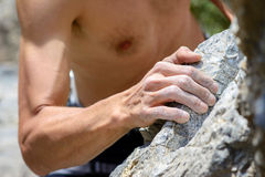Hand holding grip. Man's hand climbing on limestone. Muzzerone mountain, Liguria, Italy stock photo