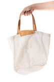 Hand holding grunge cotton bag on white background Stock Photography