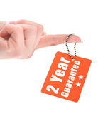 Hand holding guarantee tag Royalty Free Stock Photography