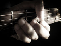 Hand holding guitar dark background Royalty Free Stock Photography