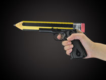 Hand holding gun with pencil point Royalty Free Stock Photos