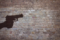 Hand holding gun. Silhouette on brick wall Royalty Free Stock Images