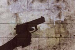 Hand holding gun silhouette. On brick wall texture Royalty Free Stock Images