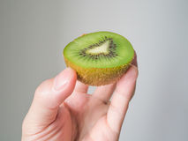 Hand holding half kiwi fruit Stock Photos
