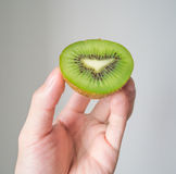 Hand holding half kiwi fruit Royalty Free Stock Photo