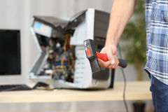 Hand holding a hammer after destroy a computer. Hand of a furious hot-tempered man holding a hammer after destroying a computer on a table Stock Photos