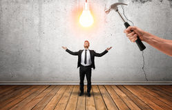 Hand holding a hammer going to break glowing bulb over businessman's head. Stock Images