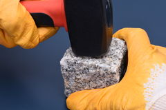 Hand holding hammer and stone block Royalty Free Stock Image