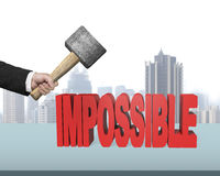 Hand holding hammer to creak impossible 3D word Royalty Free Stock Photo