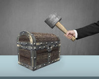 Hand holding hammer to hit old treasure chest. On desk Stock Images