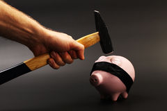 A hand holding a hammer which is raised above a upside down pink piggy bank with black blindfold standing on black background.  Stock Photo