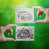 Hand holding hand drawn house and car royalty free stock image