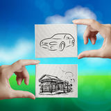 Hand holding hand drawn house and car Stock Images