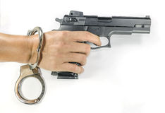 Hand holding a hand gun with handcuffs Stock Photo