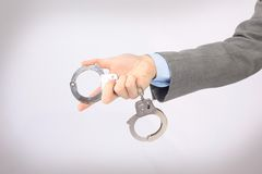 Hand holding the handcuffs. Royalty Free Stock Image