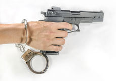Hand holding a handgun with handcuffs Stock Images
