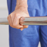 Hand holding on handle of treadmill. Old hand of senior man holding on to handle of a treadmill Royalty Free Stock Images
