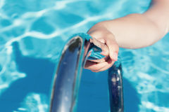 A hand holding a handrail in a swimming pool. Female`s hand holding a handrail in a swimming pool royalty free stock photos
