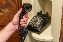 Hand using Old Rotary telephone sitting in nook in hallway stock photos