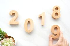 Hand holding 2019 happy new year wood letters on white marble background, 2019 new year greeting card banner stock photos
