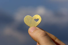 Hand Holding a Heart against the Blue Sky. Stock Photo