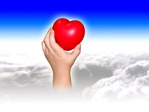 Hand holding heart over clouds. Montage of hand holding red heart above clouds with blue sky background Stock Photos