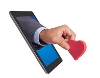 Hand holding heart shape coming from tablet Stock Photography