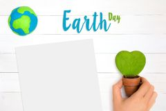 Happy mother earth day. Hand holding heart shape green plants and global planet over white wooden background with copy space. Happy mother earth day. Top view royalty free stock photos