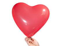 Hand holding a heart shaped balloon, isolated Royalty Free Stock Photography