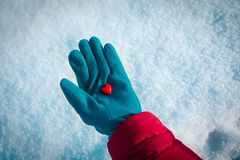 Hand holding heart in winter nature, giving love,. Valentine concept stock photo