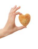 Hand holding heartshape cake Stock Images