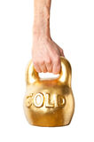 A hand holding heavy weight of gold Stock Photography