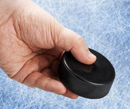 Hand holding a hockey puck Stock Photography
