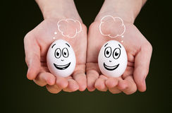 hand holding holding eggs with smiley faces Royalty Free Stock Photography