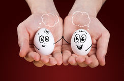 Hand holding holding eggs with smiley faces Stock Photo