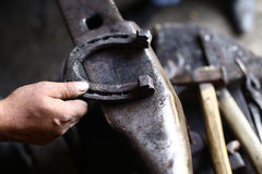 Hand holding a horseshoe on an anvil Stock Photo